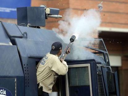 Um agente antimotim dispara bombas de gás lacrimogêneo.