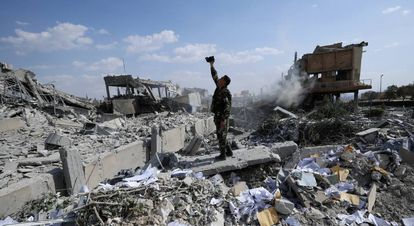 Soldado sírio filma os destroços após o bombardeio aliado.