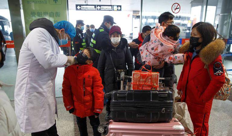 Médico mede a temperatura de passageiros antes do embarque no aeroporto de Changsha, na China.