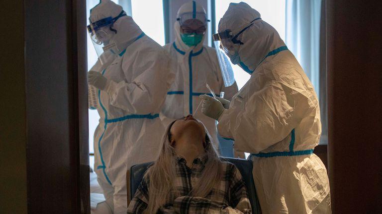 Médicos fazem exame de coronavírus numa paciente em um hotel de Wuhan.
