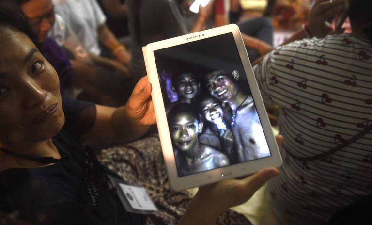 Uma familiar mostra uma foto de alguns dos desaparecidos tirada dentro da gruta pelas equipes de resgate nesta segunda-feira, na Tailândia.