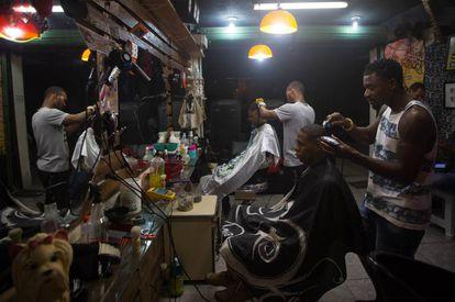 Sagat corta o cabelo de um cliente em sua barbearia, na favela da Mangueira.