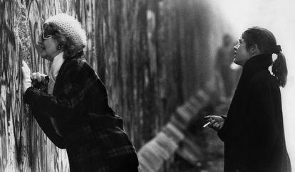 Uma mulher, que está do lado ocidental, olha através do muro de Berlim.