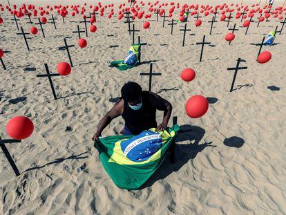 Ativista posiciona bandeira do Brasil em protesto da ONG Rio de Paz pelas vítimas do coronavírus, no Rio de Janeiro, no domingo.