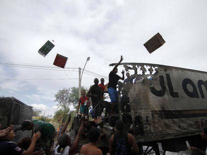 Grupo de pessoas saqueia caminhão no Rio.