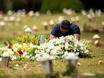AME4755. BRASILIA (BRASIL), 23/03/2021.- Un hombre visita una tumba en el cementerio Campo de Esperanza, hoy, en Brasilia (Brasil). Brasil bordea los 300.000 muertos por covid-19, mientras persiste el riesgo de desabastecimiento de medicamentos esenciales para los enfermos con cuadros más graves ante el creciente número de hospitalizaciones. EFE/ Joédson Alves.