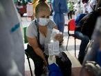 Una paciente asintomática recibe de una doctora una bolsa con cloroquina, azitromicina y dexametasona el 25 de agosto en Caracas.