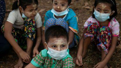 Quatro crianças assistem a um funeral em Rangum, maior cidade de Mianmar.