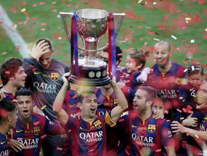 Xavi ergue a taça de campeão da Liga pelo Barcelona.