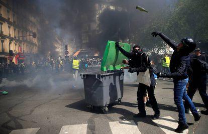 Um manifestante com capacete lança uma garrafa de vidro, durante os distúrbios deste sábado em Paris.