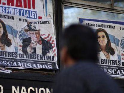 Um homem passa por cartazes que falam da crise argentina, em Buenos Aires.