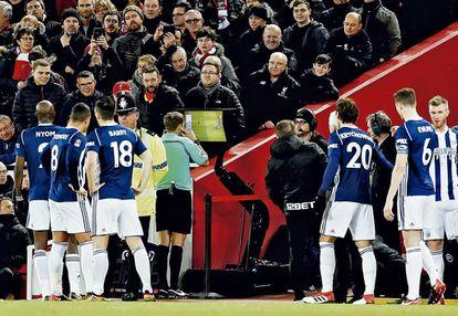 O árbitro checa o monitor VAR para conferir um pênalti a favor do Liverpool, enquanto os jogadores da equipe rival, West Bromwich Albion, aglomeram-se para assistir os replays (com um policial escoltando o árbitro, caso algum deles esteja muito chateado). Finalmente, o pênalti foi concedido, em uma partida em que o VAR também foi usado para descartar um gol da WBA, que, no entanto, ganhou por 3 x 2.