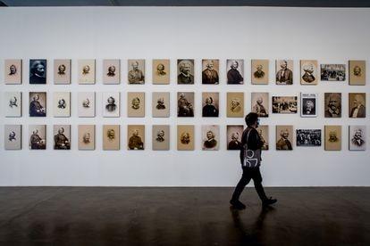 Um homem caminha em frente a uma série de retratos de Frederick Douglass na Bienal de São Paulo.
