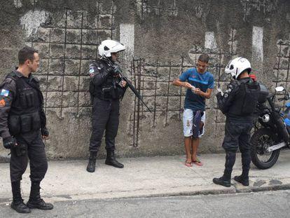 Policiais militares revistam um jovem em uma favela do Rio de Janeiro.