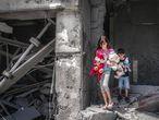 Niños palestinos rescatan juguetes de su casa, que resultó gravemente dañada por los ataques aéreos israelíes, en la Torre Al-Jawhara en Gaza, el pasado 17 de mayo de 2021.