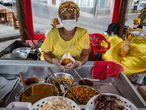 """Larissa, 26 anos, trabalha no Acarajé da Dinha, um dos tabuleiros de baiana de acarajé mais famoso do Brasil. O local passou um período fechado por causa da covid-19 e, agora, abriu de novo. """"Tenho um filho de três anos para cuidar e manter, e trabalho em segurança, usando sempre máscara e luvas. Esta é a minha única fonte de renda."""""""
