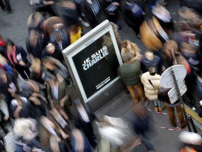 Cartaz de apoio à revista 'Charlie Hebdo' rodeado de assistentes a uma manifestação depois dos atentados.