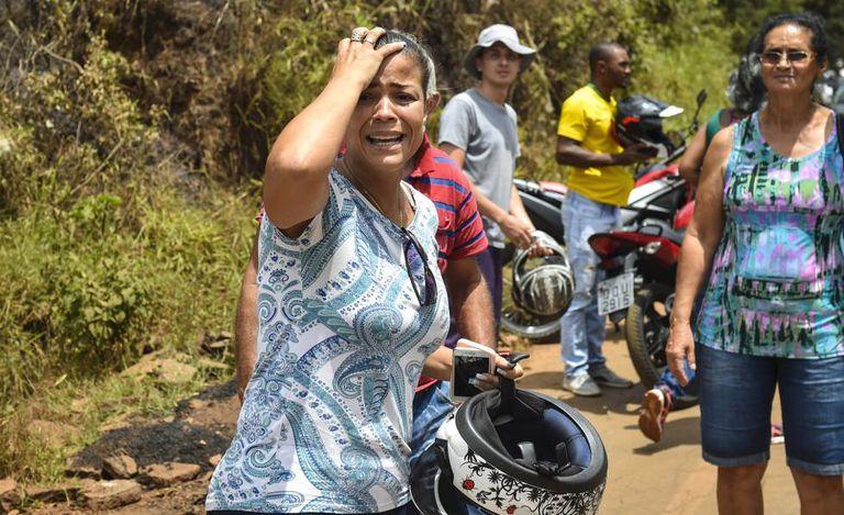 Mulher chora ao observar os estragos causados pelo rompimento da barragem em Brumadinho.