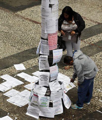 Transeuntes leem ofertas de trabalho em São Paulo.
