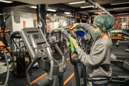 Funcionária faz limpeza dos equipamentos de uma academia.