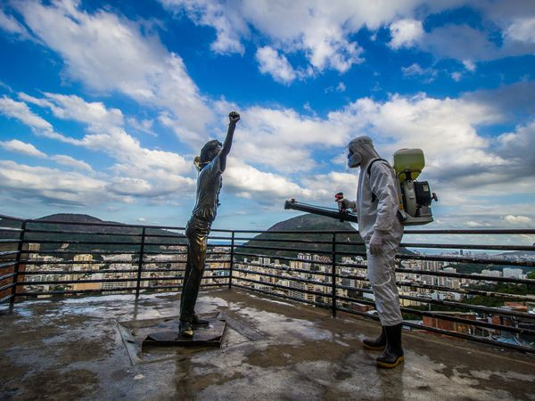 02 July 2020, Brazil, Rio de Janeiro: A man in a coverall protective suit disinfects a bronze figure at Santa Marta Favela. Brazil is second only to the United States in terms of the number of confirmed coronavirus cases. Photo: Ellan Lustosa/ZUMA Wire/dpa 02/07/2020 ONLY FOR USE IN SPAIN