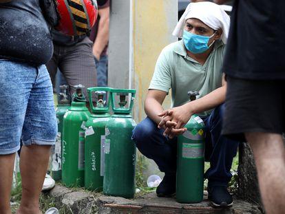 Parentes de pacientes hospitalizados ou recebendo assistência médica em casa, a maioria com Covid-19, fazem fila para comprar oxigênio e encher cilindros em uma empresa privada em Manaus