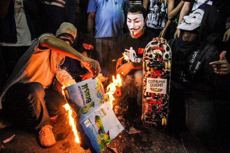 Manifestantes queimam álbum de figurinhas da Copa, nesta quinta, no Rio.