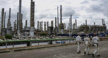Trabalhadores passeiam diante da indústria petroquímica em Camaçari, no Brasil