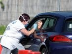 A medical worker conducts a coronavirus disease (COVID-19) check-up at a drive-thru testing site in Chessington, London, Britain, April 24, 2020. REUTERS/Henry Nicholls
