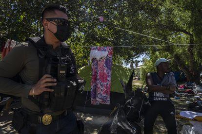 A Mexican policeman walks through the Haitian migrant camp in Ciudad Acuña, Coahuila State, on Thursday.