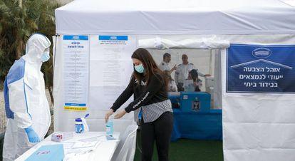 Funcionários de saúde israelenses testam um centro eleitoral para eleitores isolados pelo coronavírus, no domingo em Tel Aviv.
