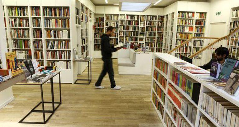 Homem caminha enquanto lê um livro na livraria Juan Rulfo, em Madri.