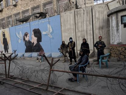 Milicianos do Talibã monta guarda em Cabul diante de um cartaz que mostra uma mulher e uma menina.