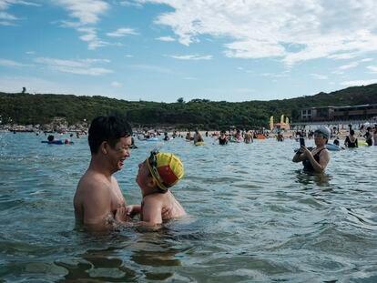 Uma criança com uma touca de natação com a bandeira da China é vista com o pai, na praia de Dongchong.