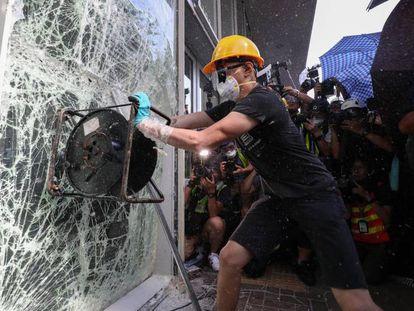 Manifestante tenta quebrar janela do Parlamento em Hong Kong, nesta segunda-feira.