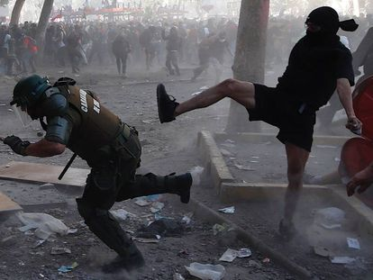 Manifestantes e policiais se enfrentam durante a manifestação em Santiago, nesta terça-feira.