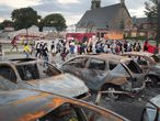 KENOSHA, WISCONSIN - AUGUST 28: A small group of peaceful demonstrators protesting the shooting of Jacob Blake march past a burned out car lot on August 28, 2020 in Kenosha, Wisconsin. Blake was shot seven times in the back in front of his three children by a police officer. The shooting has led to several days of rioting and protests in the city.   Scott Olson/Getty Images/AFP == FOR NEWSPAPERS, INTERNET, TELCOS & TELEVISION USE ONLY ==