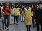 Un grupo de personas con mascarilla salen, ayer, de la estación de tren de Pekín.