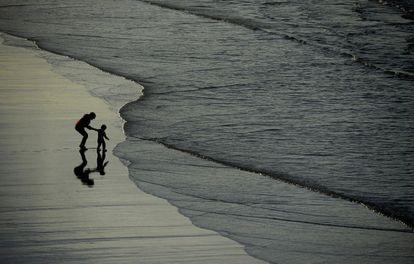 Uma mulher segura uma criança que quer alcançar as ondas na praia dos Quebrantos em San Juan de la Arena (Espanha), em 7 de novembro de 2015.