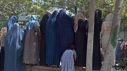 Mulheres afegãs que fugiram do avanço dos talibãs esperam para receber comida de ajuda humanitária em um parque de Cabul, na sexta-feira.