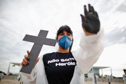 """Manifestante com a mensagem """"Não somos heróis"""" em protesto de profissionais da saúde em frente ao Palácio do Planalto, em 1º de maio."""