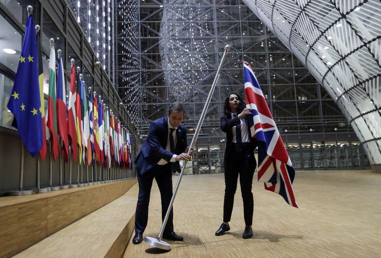 Dois funcionários retiram a bandeira britânica da sede do Conselho Europeu, nesta sexta em Bruxelas.