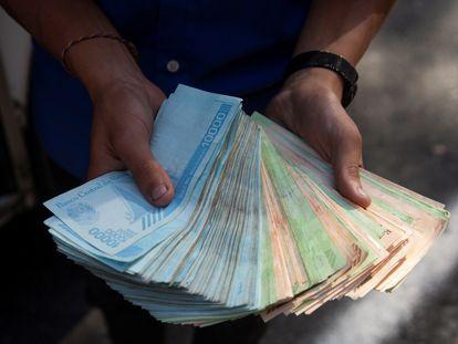 Um trabalhador dos transportes mostra um maço de bolívares, em 12 de março de 2021, em Caracas, quando uma bengala de pão custava um milhão de bolívares.