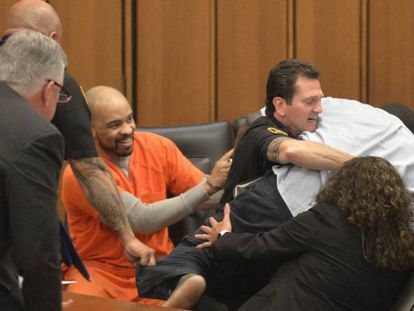 Acusado ri enquanto o pai de uma das mulheres assassinadas é contido por segurança.