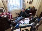 Un partidario del presidente de Estados Unidos, Donald J. Trump, se sienta en el escritorio de la presidenta de la Cámara de Representantes de Estados Unidos, Nancy Pelosi,