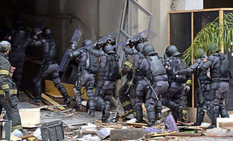 Policiais entram no hotel ocupado.
