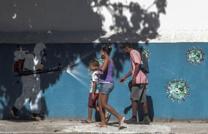 Família passa por um grafite que mostra profissional da saúde pulverizando coronavírus no rosto do presidente Jair Bolsonaro, no dia 22 de junho.