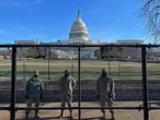 US National Guard soldiers guard the grounds of the US Capitol from behind a security fence in Washington, DC, on January 9, 2021. - US Democrats on January 9 were readying for an unprecedented second impeachment of Donald Trump as the defiant US President showed no signs of stepping down after the deadly violence at the Capitol on January 6. (Photo by Daniel SLIM / AFP)