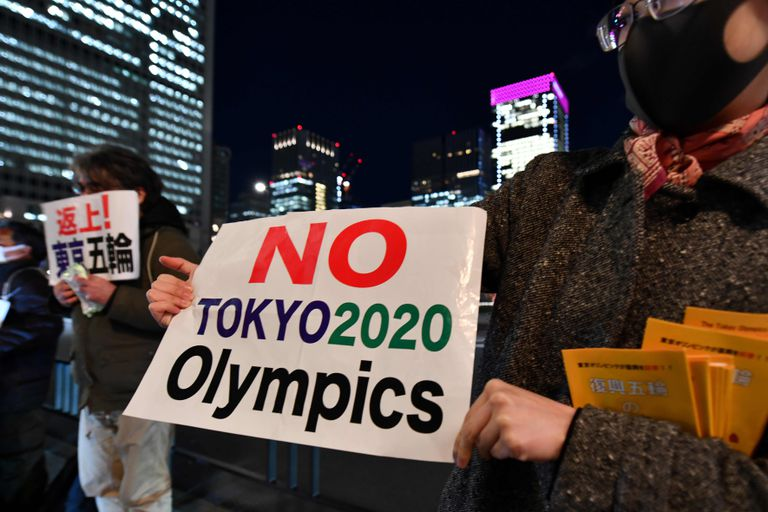 People opposed to the Tokyo 2020 Olympics display placards during a rally in front of Tokyo railway station on March 24, 2020. - The International Olympic Committee came under pressure to speed up its decision about postponing the Tokyo Games on March 24 as athletes criticised the four-week deadline and the United States joined calls to delay the competition. (Photo by Kazuhiro NOGI / AFP)