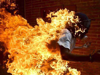 Jovem envolto em chamas durante o protesto.